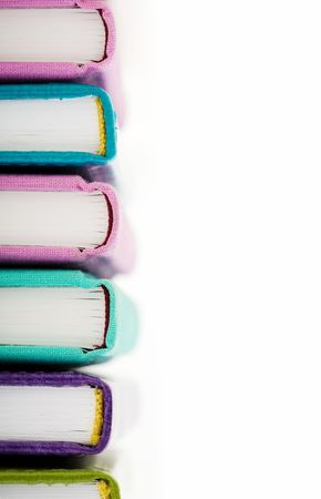 High pile of books or notepads in colorful covers over white background photo