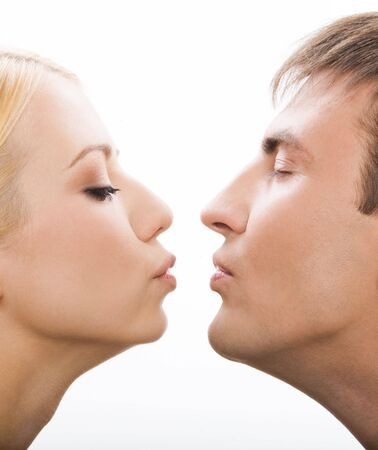 Profiles of girlfriend and boyfriend giving each other an air kiss over white background