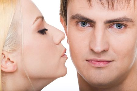 Handsome guy looking at camera with pretty girl kissing him photo
