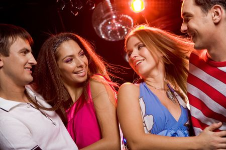 couple dating: Two excited couples looking at each other with smiles during disco