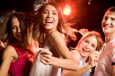 Pretty clubber dancing surrounded by her friends and looking at camera with smile Stock Photo - 3858397