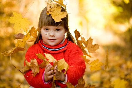 Portrait of small girl catching falling leaves in autumn forest photo