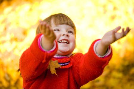 enfants qui rient: Cute girl de rire et de jouer avec les feuilles d'automne dans le parc