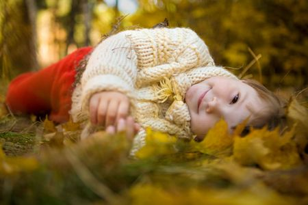 Cheerful girl lying on her side surrounded by leaves and looking at camera photo