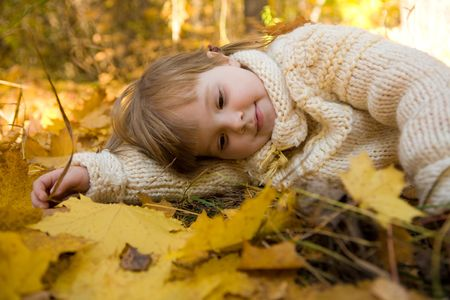 Tired girl relaxing on autumn ground covered with dry maple leaves photo