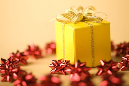 Small yellow package with golden bow on top surrounded by chain of red decorative stars Stock Photo - 3884410