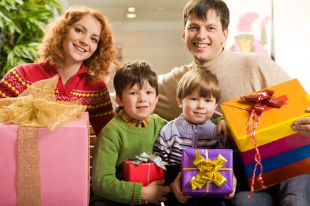 glad: Portrait of glad family members with lot of gifts sitting in supermarket after shopping Stock Photo