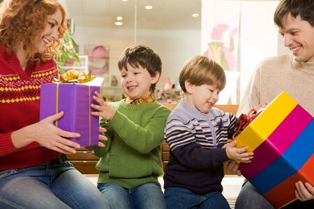 Photo of surprised children being given wonderful gifts by their parents Stock Photo - 3883199