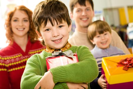 Portrait of glad boy with present looking at camera on background of family members Stock Photo - 3883187