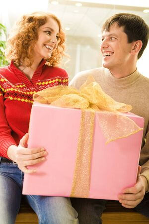 Portrait of smiling couple holding big pink gift box and looking at each other photo