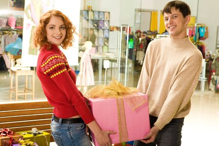 Cheerful couple carrying big box with presents for all family in supermarket photo