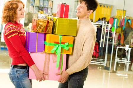 Portrait of shopaholics holding heap of presents and wondering what to do next photo