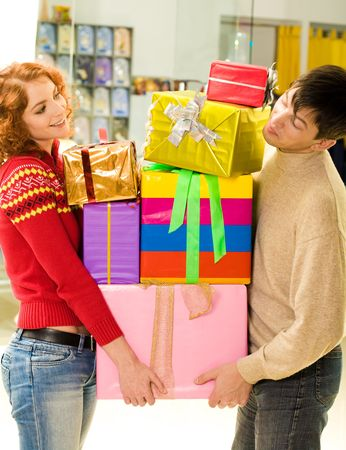 Husband and wife standing with pile of boxes after doing great shopping photo