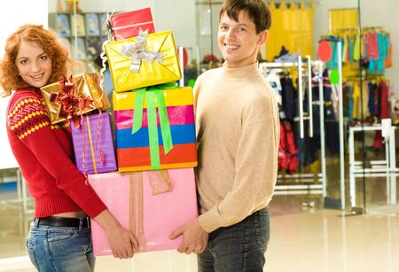 Photo of two smiling people carrying colorful boxes and looking at camera in shopping mall photo
