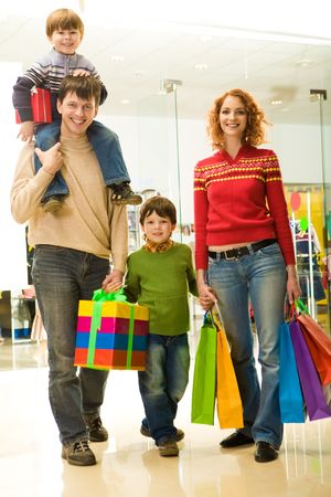 Portrait of family walking down shopping mall after buying Christmas presents Stock Photo
