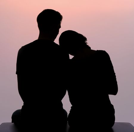 back: Outline of loving woman putting her head onto shoulder of man sitting next to her Stock Photo