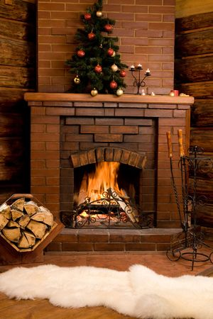 Photo of fireplace with firewood and warm white fur near by photo