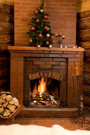 christmas fireplace: Image of hot fire in chimney with fir tree decorated before Christmas Stock Photo