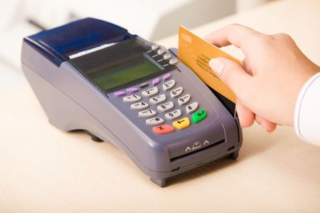 business transaction: Photo of shop assistant�s hand with credit card during financial operation