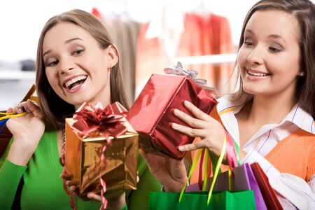 Pretty girls looking at nice presents in their hands and laughing happily photo