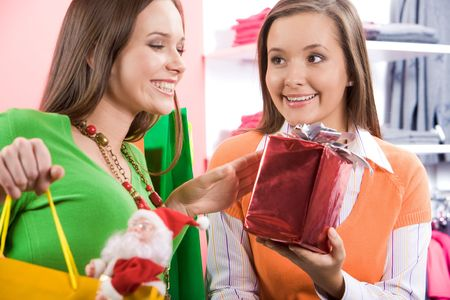 Glad customer looking at wrapped gift being offered to her by helpful shop assistant photo