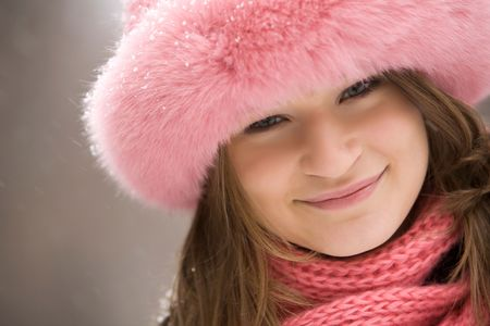 Face of pretty woman wearing pink winter fur cap and looking at camera with smile photo