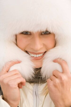 Portrait of beautiful female wearing pure white fur cap and smiling photo