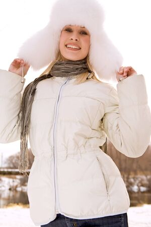 Portrait of young woman wearing white fur cap and warm jacket in winter photo
