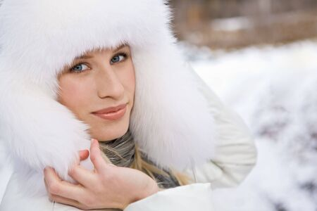 Pretty woman in white fur cap touching it and looking at camera photo