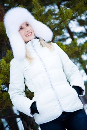 Portrait of charming female wearing winter clothing and having walk in forest photo