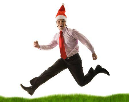 Portrait of businessman in santa cap running down green grass on white background photo