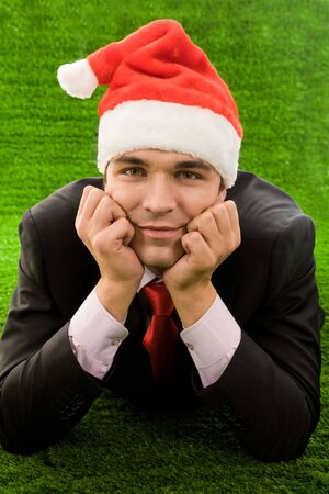 Businessman in santa cap touching his face by hands while relaxing on green grass Stock Photo - 3929309