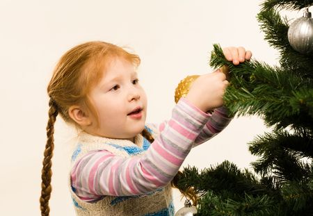 Photo of pretty red-headed girl hanging nice toys on fir tree branches photo