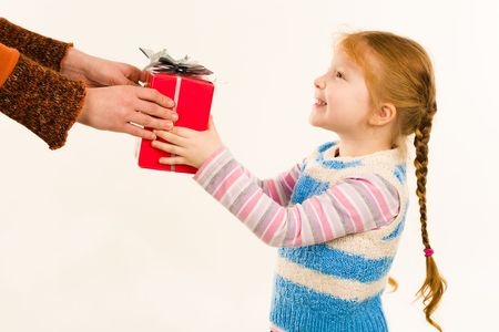 Little girl taking Christmas present from female hands over white background Stock Photo - 3929270