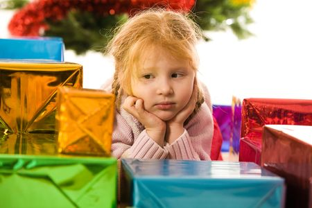 Thinking girl touching her face with pensive expression on it while looking at heap of colorful presents photo