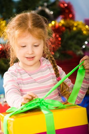 Photo of curious girl undoing green ribbon on giftbox to find her present photo