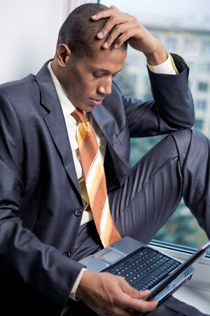 african boy: Photo of handsome employee working in office with laptop in front