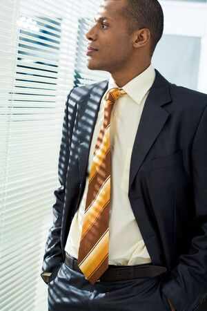 Serious businessman standing and looking through venetian blind in office photo