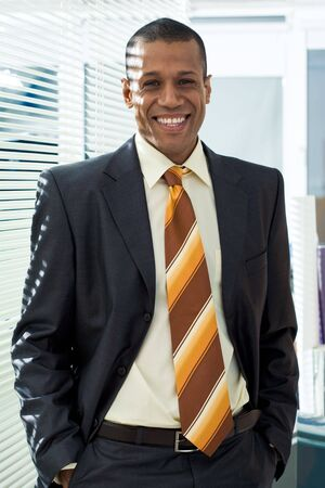 Portrait of happy man in suit standing near venetian blind in office photo
