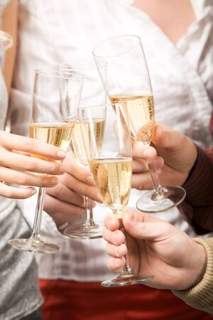Close-up of friends hands holding glasses with champagne and making cheers Stock Photo - 3931547