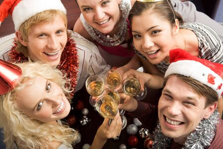 male friends: View from above of merry friends with flutes of champagne looking upwards