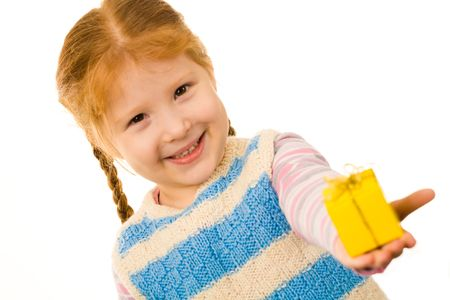 kid: Little redheaded girl giving somebody small present in yellow box and smiling Stock Photo