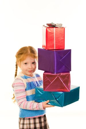 Portrait of little girl with pile of Christmas gifts in hands looking at camera photo