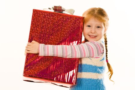 glad: Image of glad child embracing very big giftbox with her present and smiling Stock Photo