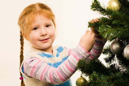 Photo of little girl near fir tree decorating it and looking at camera photo