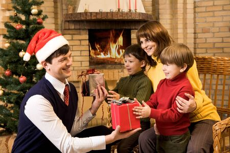 Photo of happy father giving Christmas gifts to surprised sons on holiday eve photo