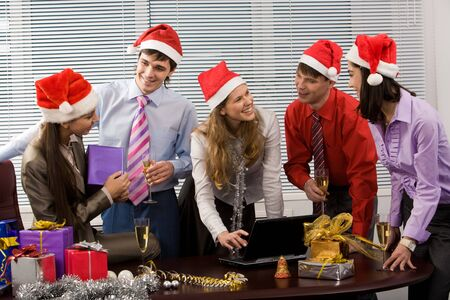 Portrait of friendly business team wearing Santa caps while communicating in office photo