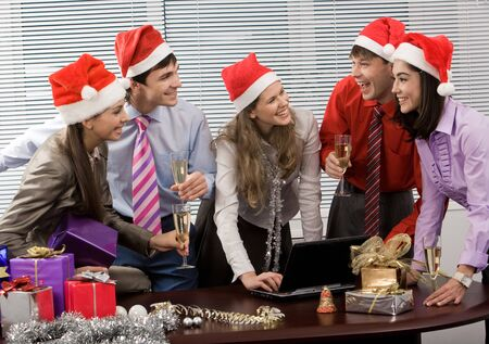 holiday gathering: Photo of laughing co-workers interacting during corporate party in office Stock Photo