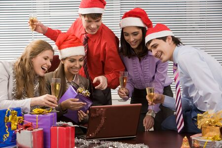 Image of joyful business group looking at screen of laptop and reading greets with smiles photo