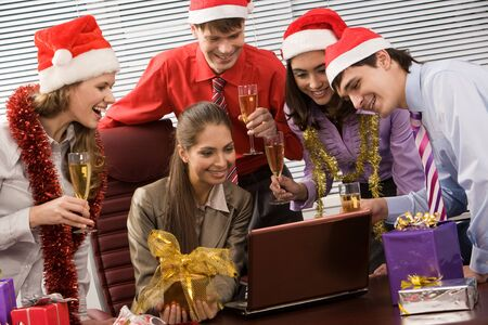Photo of attractive co-workers with champagne in hands looking at laptop display  photo